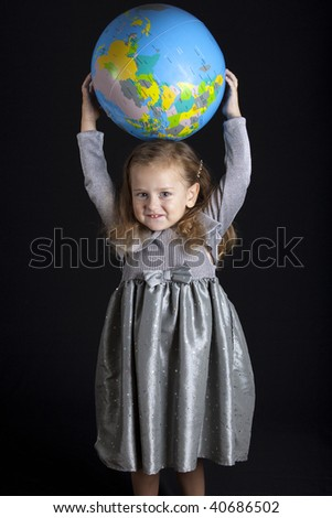 Beautiful girl standing with globe, studio shot