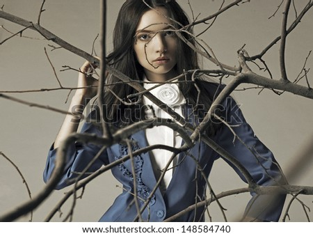 beautiful girl stands in the branches
