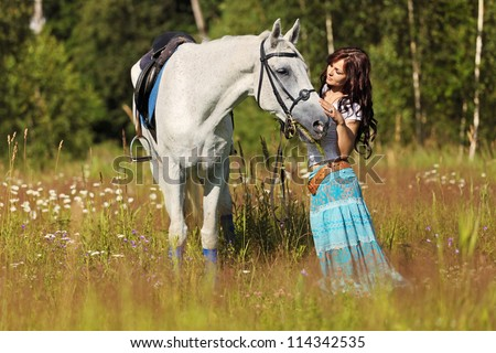 Beautiful girl stands on white horse on a summer meadow