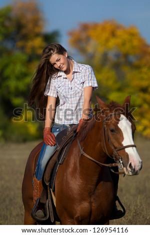 Beautiful girl  straddling a horse in garden