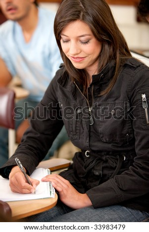 Beautiful girl studying and writing on her notebook in the classroom