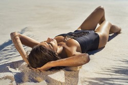 Beautiful girl sunbathing on a sandy tropical beach. Fashion young woman lying on back on sand with black swimsuit. Tanned woman relaxing at sea under the shade of palm leaves.