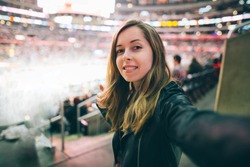 Beautiful girl supporter taking selfie self-portrait while watching basketball game at the stadium