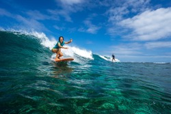 beautiful girl surfing on big transparent waves