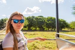 Beautiful girl taking a safari tour bus through the national park of Casela on Mauritius island