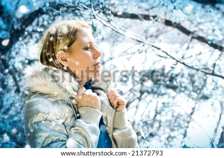 beautiful girl taking a walk in a winter forest