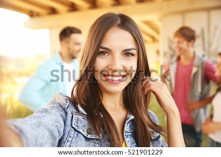 Beautiful girl taking selfie on street