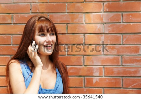 Beautiful girl talking on cellular phone outdoors on red brick wall background