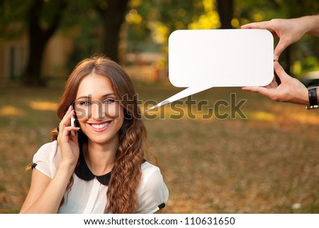 Beautiful girl talking with cell phone in park