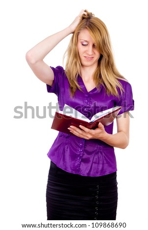 Beautiful girl thinks, looking in a book isolated on white background