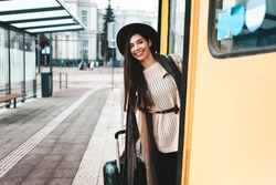 Beautiful girl tourist in coat and hat peek out of a tram door