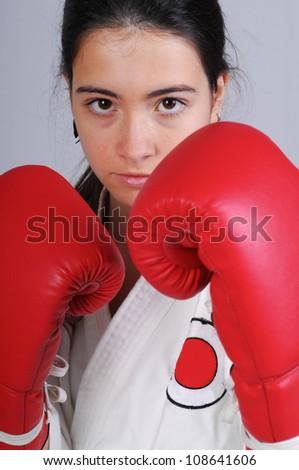 beautiful girl training combat with boxe gloves, studio photo