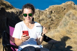 Beautiful girl traveler using smartphone, holding iron mug cup of coffee, sitting in touristic chair on cliff near ocean outdoors.Checking social media, chatting with friend,reading news,sharing data