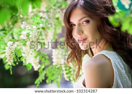 Beautiful girl under blossom acacia tree