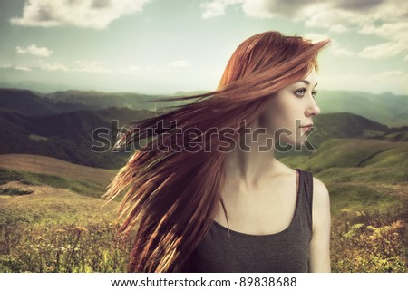 beautiful girl upland with hair blown by wind