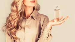 Beautiful girl using perfume. Woman with bottle of perfume. Woman presents perfumes fragrance. Perfume bottle woman spray aroma. Woman holding a perfumes bottle. Womans with perfum bottle.