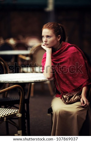 beautiful girl waiting at a table in a cafe - stock photo
