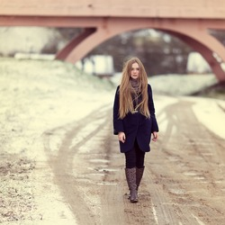 Beautiful girl walking along a winter road near the bridge. Portrait in full growth