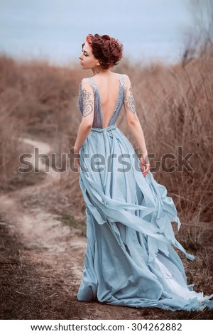 Beautiful girl walking in nature.  Fancy Dress with train in the style of Shabby Chic. Fashionable toning. Background late autumn, river, cold.