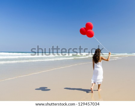 Beautiful girl walking in the beach and holding red balloons