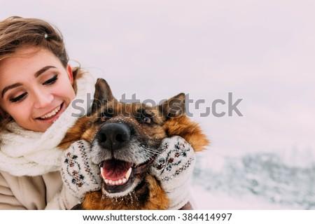 Beautiful girl walking on a winter walk with her big dog #384414997