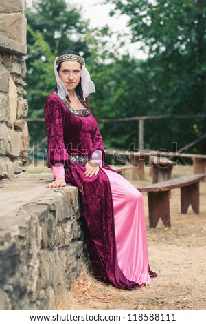 Beautiful girl wearing a burgundy medieval dress. Full body.