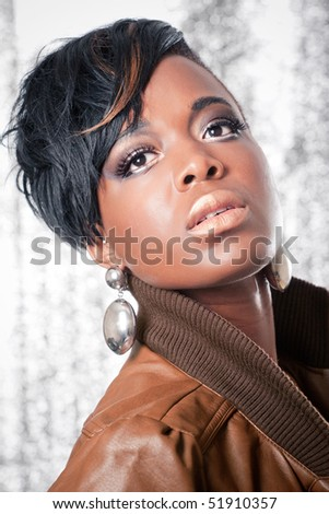 Beautiful girl wearing a leather jacket, studio portrait on shiny background