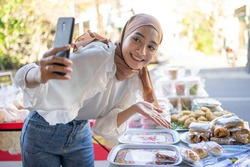 Beautiful girl wearing a smiling hijab using a mobile phone offers a variety of fried foods online at roadside stalls