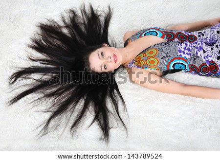 Beautiful girl wearing dress lies on white fur inside studio #143789524
