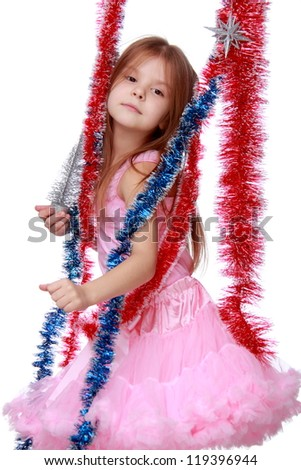 Beautiful girl wearing light pink top and tutu skirt and artificial tinsel over her on Christmas theme