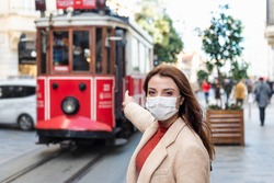 Beautiful girl wearing protective medical mask and fashionable clothes shows nostalgic tramway at istiklal street, Istanbul,Turkey. New normal lifestyle concept.