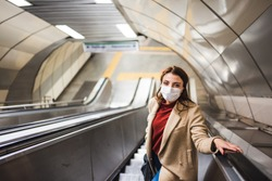 Beautiful girl wearing protective medical mask and fashionable clothes uses stairs for subway.New normal lifestyle concept.