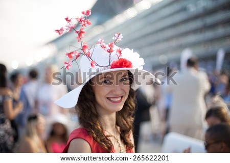 Beautiful girl wearing Sakura flower hat smiling at the Dubai World Cup Horse Race
