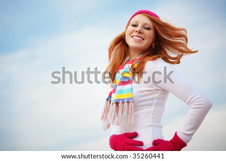 Beautiful girl wearing winter clothing over sky