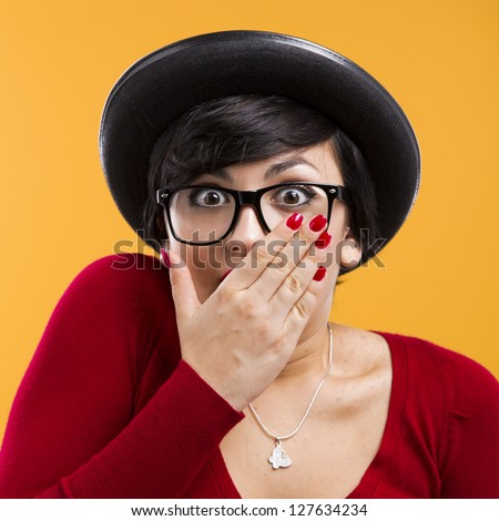 Beautiful girl with a astonished expression, wearing a hat and nerd glasses over a yellow background