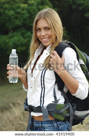 Beautiful girl with a backpack, drink mineral water.