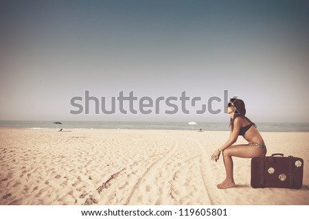 Beautiful girl with a bag in a beach