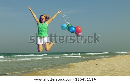 Beautiful girl with a balloons on the beach. Old style colors.