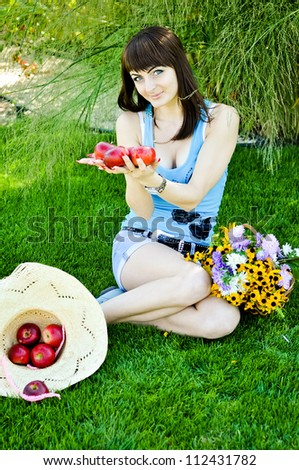 Beautiful girl with a basket of flowers and apples on a lawn