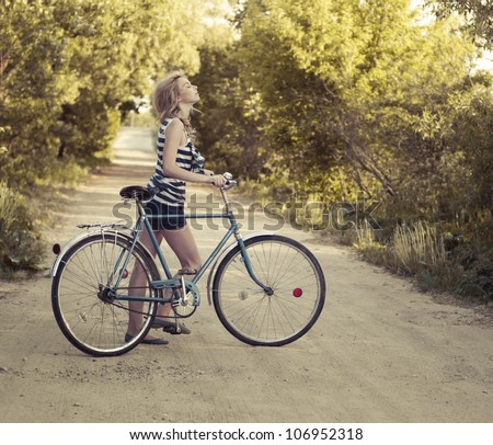 beautiful girl with a bicycle on the road