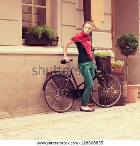 beautiful girl with a bicycle on the street of the old town - stock photo