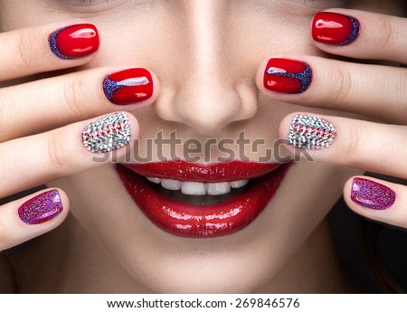 Beautiful girl with a bright evening make-up and  manicure with rhinestones. Nail design. Beauty face. Picture taken in the studio on a black background.