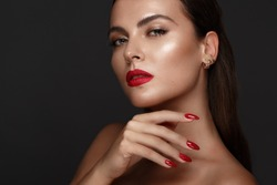 Beautiful girl with a classic make up and multi-colored nails. Manicure design. Beauty face. Photo taken in the studio