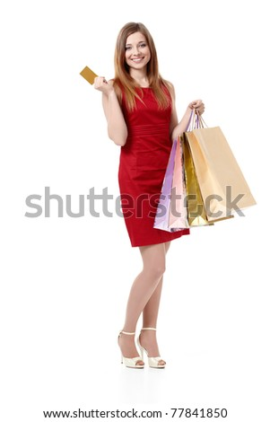 Beautiful girl with a credit card and shopping bags on white background