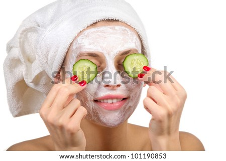 Beautiful girl with a mask and cucumber slices on his face on a white background