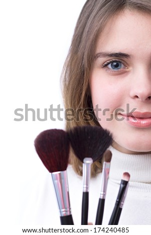 beautiful girl with a set of brushes for makeup in her hands