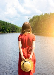 Beautiful girl with a straw hat near the lake. Amazing summer nature. Travel concept. Inspiration for wanderlust. Woman in linen red dress. Eco-friendly materials for clothes.