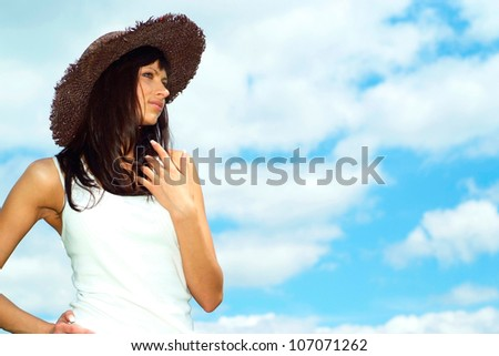 Beautiful girl with a sweet expression on her  face against the blue sky with clouds #107071262