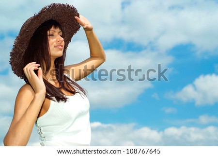 Beautiful girl with a sweet expression on her  face against the blue sky with clouds #108767645