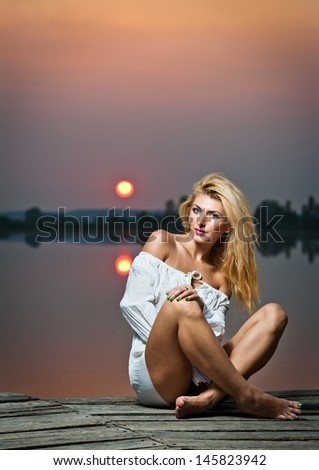 beautiful girl with a white shirt on the pier at sunset.Sexy woman with long legs sitting on a pier .Color image of a beauty girl sitting on a pier, overlooking a lake